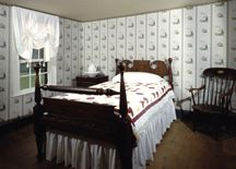 A bedroom, with the Woodville-pattern wallpaper.