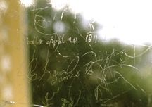 Signatures and brief messages are scratched into the window panes.